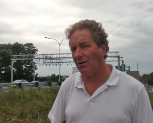 Protest organizer John Vitkevich in front of the toll gantry at the Sakonnet River Bridge.
