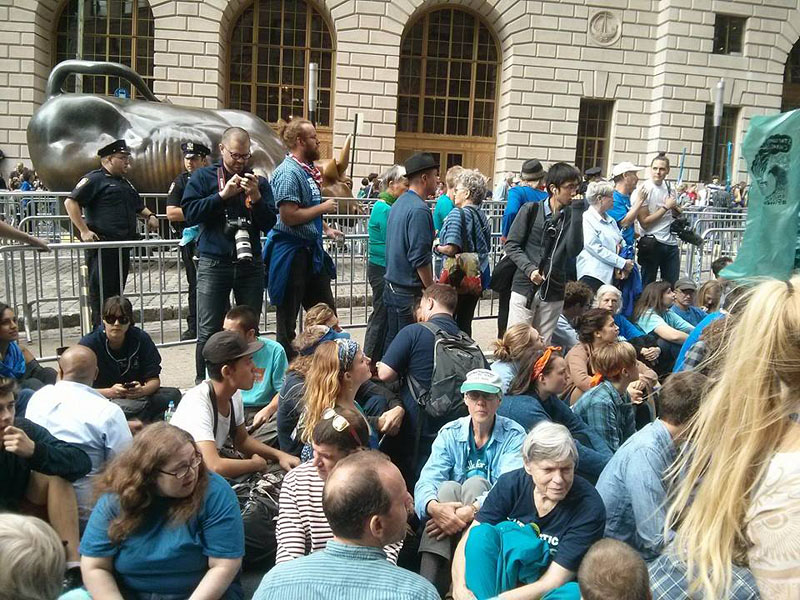 Flood Wall Street protesters stage sit-in on Broadway near the famous Wall Street Bull
