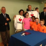 Gov. Raimondo and Sen. Whitehouse with YMCA campers after signing the healthcare reform executive order