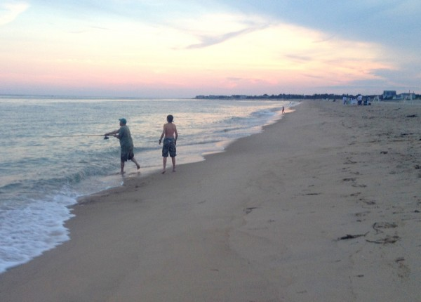 A father and son vacationing at East Beach go fishing at dusk, Aug. 2013. (Photo by Bob Plain)