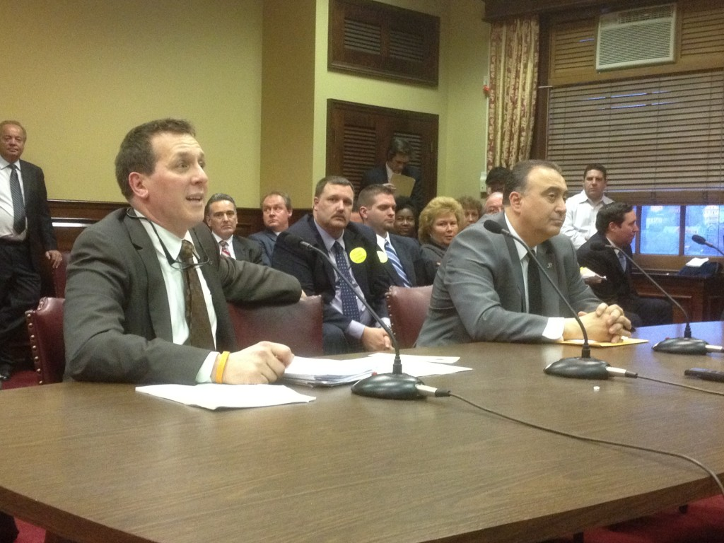 Rep. Frank Ferri testifies on his bill that would reform paypay loans in RI. In the background is Bill Murphy, former House speaker, a lobbyist opposed to the reform.