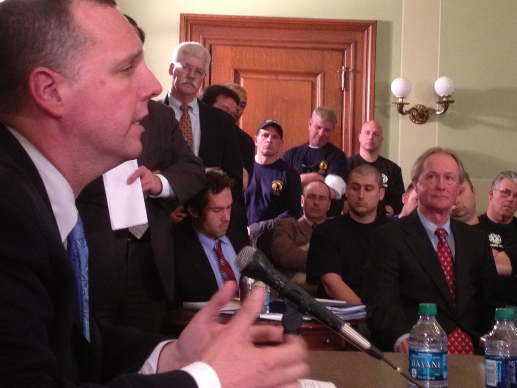 Chafee listens as Pawtucket Mayor Don Grebien speaks at the State House.
